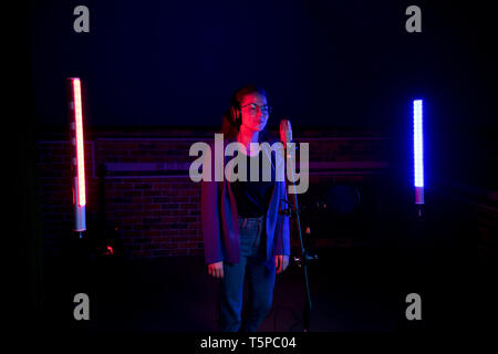 Backstage. A young woman in glasses standing by the microphone in neon lighting - Stock Image
