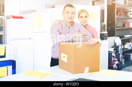 Positive smiling couple  with packed purchases in  household appliances section in shop - Stock Image
