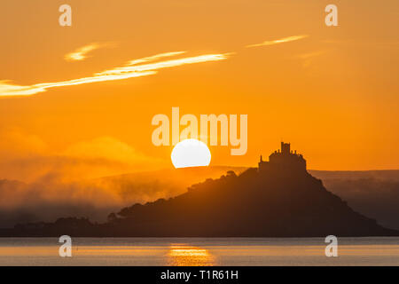 Penzance, Cornwall, UK. 28th Mar, 2019. UK Weather. The sun rises above St Michaels Mount, with mist rolling in from the land this morning. Credit: Simon Maycock/Alamy Live News - Stock Image