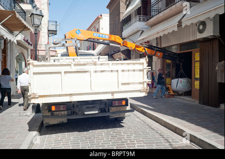 Lorry with hydraulic arm unloading large bag of sand into shop Rethymno Crete Greece - Stock Image