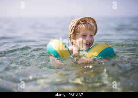 A small toddler boy with armbands swimming in water on summer holiday. - Stock Image