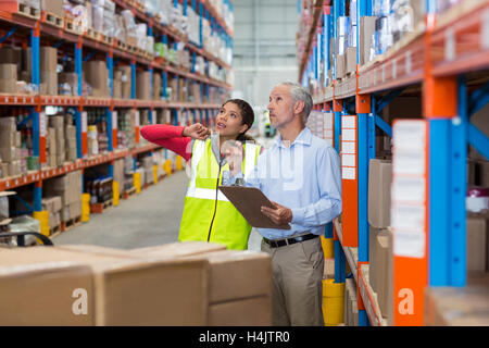 Warehouse manager and female worker interacting while checking inventory - Stock Image
