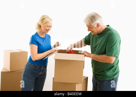 Middle aged couple packing or unpacking moving boxes - Stock Image
