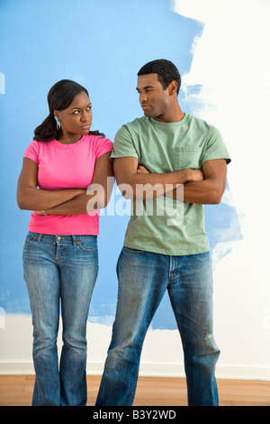 African American couple glaring at each other with anger next to half painted wall - Stock Image