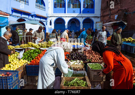 Chefchaouen, Morocco : Moroccan women shop for fruit and vegetables at Plaza Bab Suk market square, in the blue-washed medina old town. - Stock Image