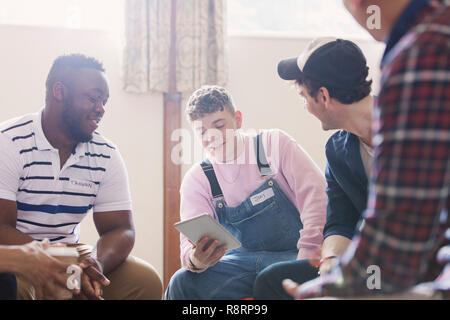 Men with digital tablet talking in group therapy - Stock Image