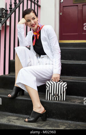 Woman in white culotte suit sitting on steps outside a house - Stock Image