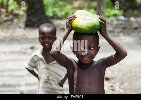 Boy with locally grown papaya on the Turtle Islands, Sierra Leone. - Stock Image