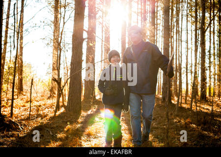 Father and son hiking in woods - Stock Image