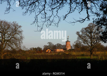 An old windmill without any sails, in Cheshire seen through winter bare leafed trees - Stock Image