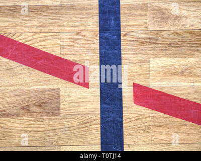 Black lines in play court on wooden lamino floor. Worn out brown wooden floor panels of sports hall - Stock Image
