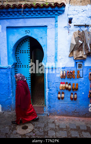 Chefchaouen, Morocco : A woman walks past a traditional wooden door in the blue-washed medina old town. - Stock Image