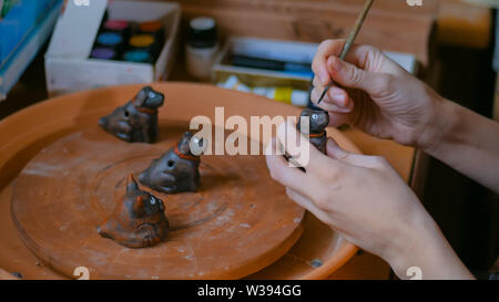 Professional woman potter painting ceramic souvenir penny whistle in workshop - Stock Image