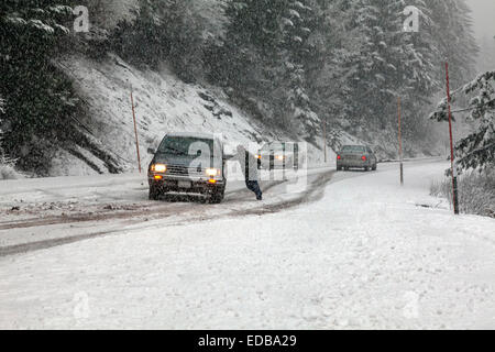 Man on foot pushes car in effort to guide vehicle's slide on snowy road during snowstorm, Tombstone Pass, Oregon, - Stock Image