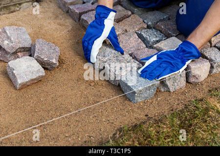 cobblestone installation - paver laying granite stone pavers - Stock Image