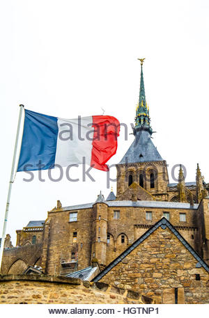 Mont St Michel on a cloudy & wet day in Normandy, France. Image shows the French flag (tricolour) with the Abbey - Stock Image