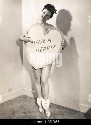 Naked woman covered by a heart-shaped sign - Stock Image