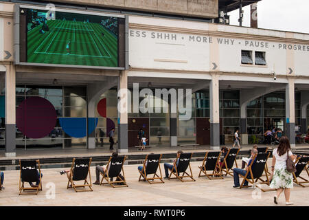 People sitting on deckchairs and watching tennis matches of Wimbledon Championships, Millennium Square, Bristol, UK - Stock Image