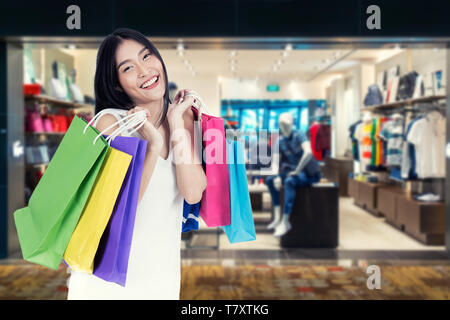 Beautiful Asian woman with shopping bags in clothes shop. Sale, shopping, tourism and happy people concept - Stock Image