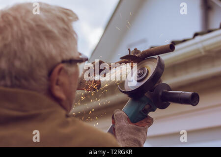 Sparks fly from grinding machine in the process of cutting metal. - Stock Image