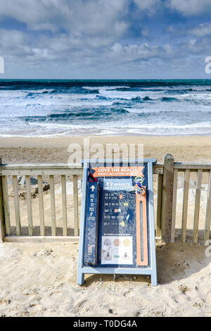 A sign encouraging people to pick up litter on Fistral Beach in Newquay in Cornwall. - Stock Image