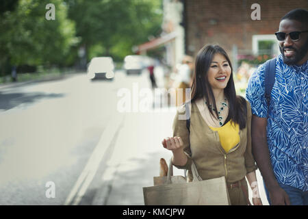 Smiling young couple with shopping bag walking on sidewalk - Stock Image