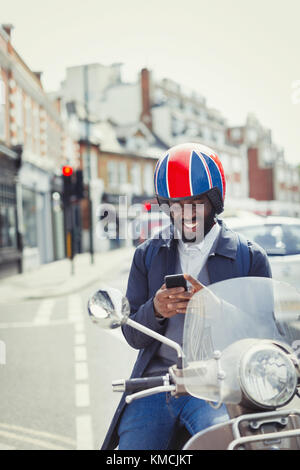 Smiling young businessman in helmet on motor scooter, texting with cell phone on urban street - Stock Image