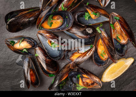 Marinara mussels, moules mariniere, with lemon slices, overhead close-up view, shot from the top on a black background - Stock Image