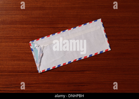 An air mail postage envelope slightly worn and torn on a wood surface. - Stock Image
