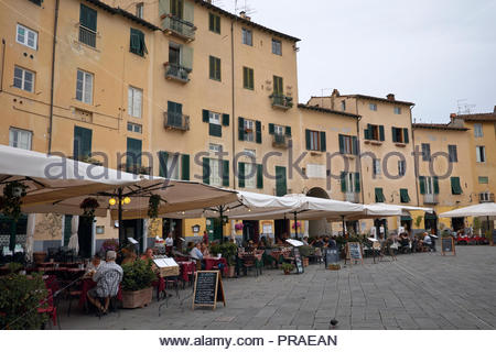 Popular restaurants and menu boards in the  Piazza dell Anfiteatro: Lucca, Italy. - Stock Image