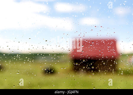 Rain drops and condensation on a glass window with a unfocused house and home behind with clear blue skies and white - Stock Image
