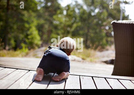 Baby boy crawling on porch - Stock Image