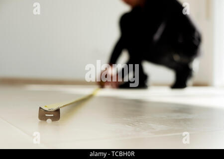 closeup of a young caucasian man using a measuring tape on a beige tiled floor - Stock Image