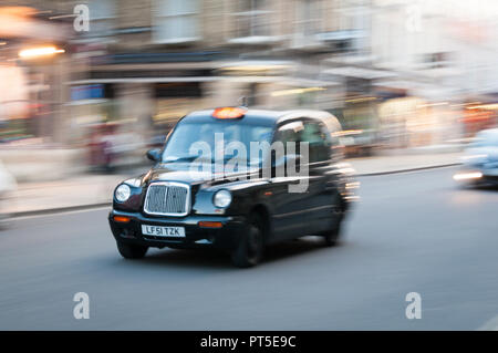Moving London black cab taxi in street - Stock Image