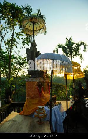 sunrise rising sun shining through ceremonial umbrella Hindu shrine, Keliki, Bali, Indonesia - Stock Image