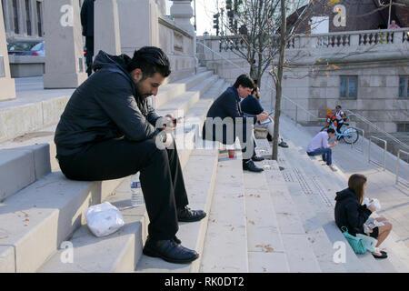 People engrossed in their cell phones. Chicago Riverwalk. - Stock Image