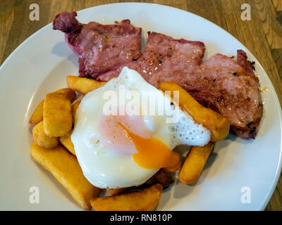 Lunch in a  Yorkshire cafe gammon egg and chips with the egg yolk cut open - Stock Image