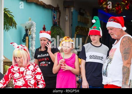 Benidorm, Costa Blanca, Spain, 25th December 2018. British tourists dress for the occasion on Christmas Day in this favourite getaway destination for Brits escaping the cold weather at home. Temperatures will be in the mid to high 20's Celsius today in this mediterranean hotspot. Family with kids outside wearing Christmas clothing and hats. - Stock Image
