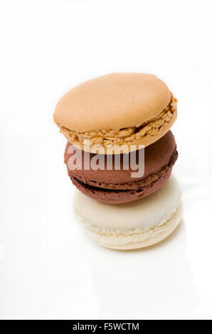 Vanilla, Chocolate, and Salted Caramel macaroons stacked on white ceramic. - Stock Image