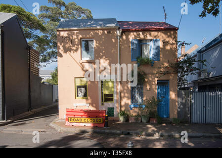A narrow street corner with two colourful double story attached terrace houses in Surry Hills, Sydney Australia - Stock Image