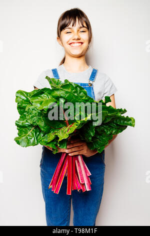 Happy girl in denim overalls holding a bunch of fresh swiss chard. Focus on the leaves - Stock Image