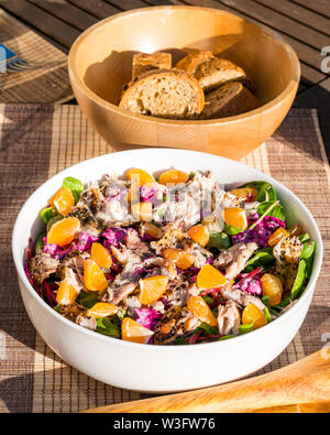 Summer food: mackerel salad meal swith clementines and beetroot served outdoors in white crockery with sliced bagueete bread in wood bowl - Stock Image