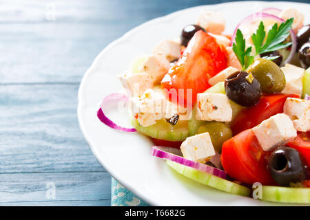 Fresh greek salad with tomato, cucumber, purple onion, feta cheese and olives on a blue wooden table - Stock Image