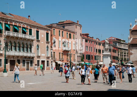 People in summer clothes enjoying June sunshine in Campo San Stefano Venice Italy  Statue of Niccolo Tommaseo is - Stock Image