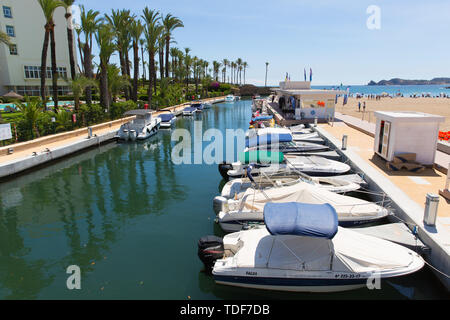 Playa del Arenal beach with boats moored in summer with blue sky - Stock Image