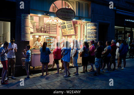 Hungry tourists queue up for cakes and ices in St Malo, Brittany, France - Stock Image