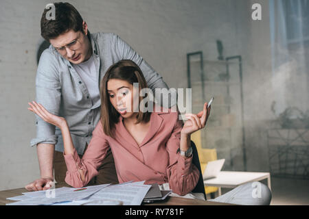 woman holding cigarette while looking at charts and graphs near concentrated man - Stock Image