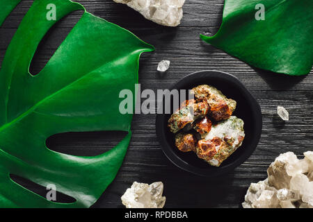 Garnet with Smoky Quartz and Monstera on Black Wood - Stock Image