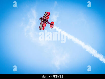 Red plane with propeller flying upward with white smoke on the tail in the blue sky - Stock Image