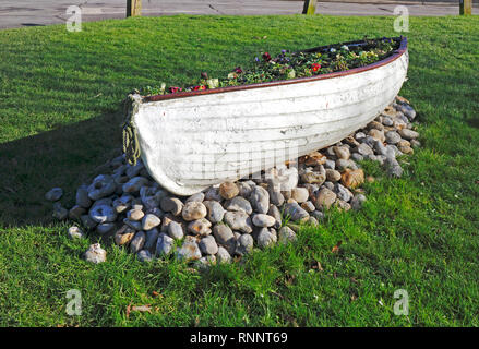 A dinghy used as a flowerbed container on the village green at Winterton-on-Sea, Norfolk, England, United Kingdom, Europe. - Stock Image